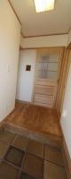 足ざわりのいいタイルの玄関、奥は家族用玄関にもなる下足室
