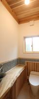 トイレ タイル、手洗鉢を落ち着いた色、デザインでまとめ、一枚板カウンターと静かに収まっています。